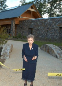 Mary Lea Simpkins cuts the ribbon to open the A.E. Finley Center for visitors at Historic Yates Mill County Park in 2006.